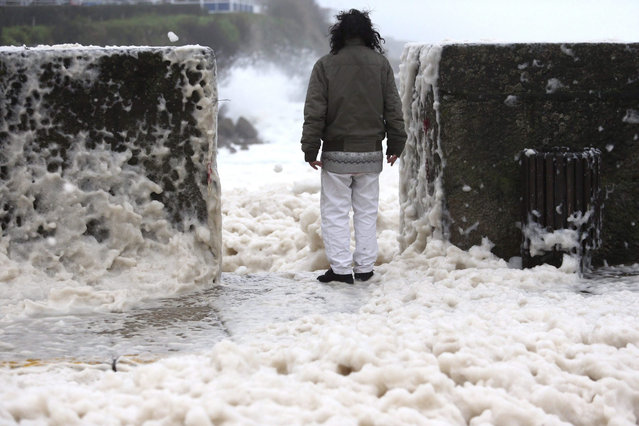 A man looks at the sea's foam at the promenade in A Guarda, Pontevedra, northwestern Spain, 10 January 2016. Rough winds and huge waves will be affecting the north of the country due to the storm striking that will leave heavy rains too. (Photo by EPA/Sxenick)
