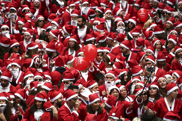 People wearing Santa Claus costumes gather to take part in the 2016 Athens Santa Run in Athens, Sunday, December 4, 2016. Several hundreds of people run in the charity event around the streets of central Syntagma square. (Photo by Yorgos Karahalis/AP Photo)