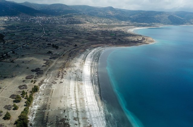 This aerial picture taken April 9, 2021, shows the shore of the southwestern Turkey Salda lake, in Burdur province. NASA believes the lake could offer clues to a crater on Mars but environmental activists fear the natural phenomenon with its bright white sand and sparkling turquoise waters is at risk (Photo by Bulent Kilic/AFP Photo)