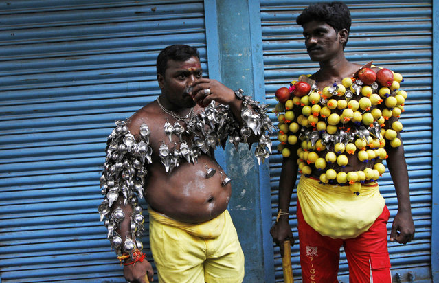 Hindu devotees, their bodies pierced with lemon and paladai, or bowl with a spout mainly used to feed milk to infants, wait to participate in a procession to mark Shivratri, or the night of Shiva, in Chennai, India, Wednesday, February 18, 2015. (Photo by Arun Sankar K./AP Photo)