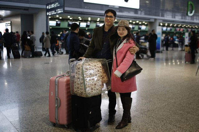 Li and his wife Zhang pose for a portrait at Hongqiao airport in Shanghai, February 12, 2015. The couple travelled to Henan province by plane to spend Chinese New Year with his family. (Photo by Carlos Barria/Reuters)
