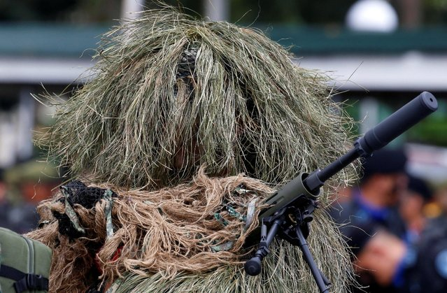 A soldier in a sniper camuoflage holds a weapon before the start of a parade for the change of command for the new Armed Forces chief at a military camp in Quezon City, Metro Manila, Philippines December 7, 2016. (Photo by Erik De Castro/Reuters)