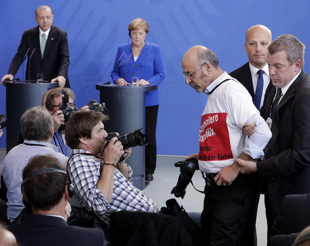 A protester is taken away as Turkish President Recep Tayyip Erdogan and German Chancellor Angela Merkel, right, give a joint press conference in Berlin, Germany, Friday, September 28, 2018. Erdogan is on a three-day official state visit to Germany. (Photo by Michael Sohn/AP Photo)