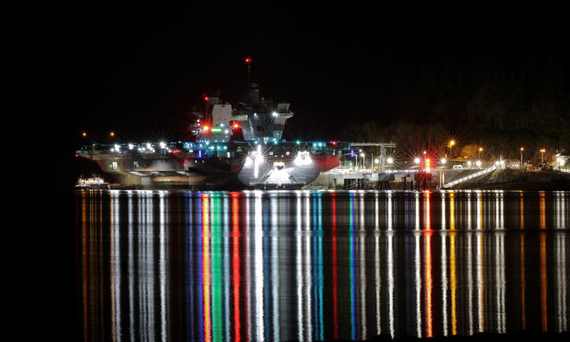 HMS Queen Elizabeth, the Royal Navy's fleet flagship, docked at night as part of final preparations before her first operational deployment in Glen Mallan, United Kingdom on March 19, 2021. (Photo by POPhot JJ Massey/PA Wire Press Association)