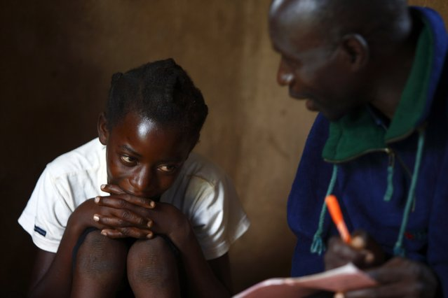 11-year-old Sonia Matanga (L), who was born HIV-positive, attends a self-help group meeting with caregiver Davison Mungoni (R) in the village of Michelo, south of the Chikuni Mission in the south of Zambia February 23, 2015. (Photo by Darrin Zammit Lupi/Reuters)