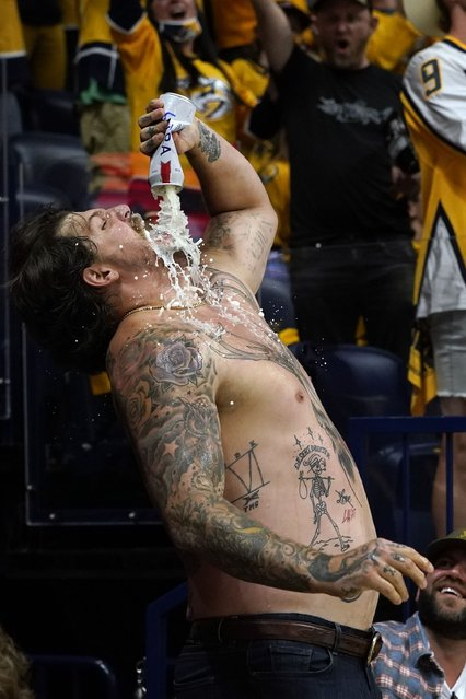 Tennessee Titans NFL football offensive lineman Taylor Lewan celebrates after a goal by the Nashville Predators during the second period in Game 4 of an NHL hockey Stanley Cup first-round playoff series between the Predators and the Carolina Hurricanes Sunday, May 23, 2021, in Nashville, Tenn. (Photo by Mark Humphrey/AP Photo)
