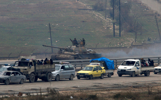 Forces loyal to Syria's President Bashar al-Assad sit on a tank as a convoy of buses and other vehicles bringing people out of eastern Aleppo turns back in the direction of the besieged rebel enclave, Syria December 16, 2016. (Photo by Omar Sanadiki/Reuters)