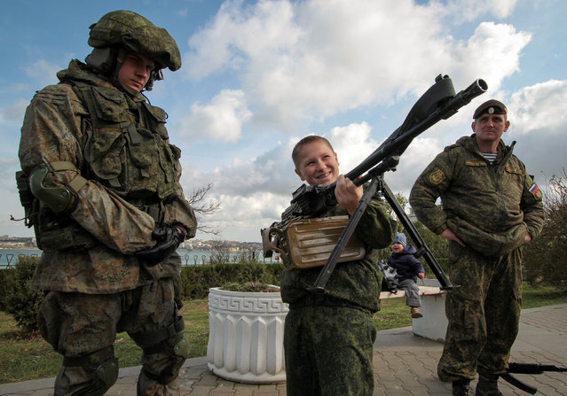 "A boy holds a machine gun at a military hardware exhibition during a swear-in ceremony for new recruits of the Russian military-patriotic club ""Yunarmia"" (Young army) in the Black Sea port of Sevastopol, Crimea, October 27, 2018. (Photo by Pavel Rebrov/Reuters)"
