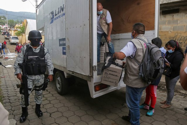 Members of the National Guard look on as vehicles arrive carrying voting booths and electoral boxes ahead of midterm elections in Nahuatzen, Mexico, June 5, 2021. (Photo by Alan Ortega/Reuters)