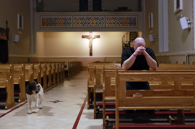 Fr Pierre Pepper prays in St Rynagh's church with his rescue dog Cosmo at dawn in the village of Banagher County Offaly February 13, 2015. (Photo by Cathal McNaughton/Reuters)
