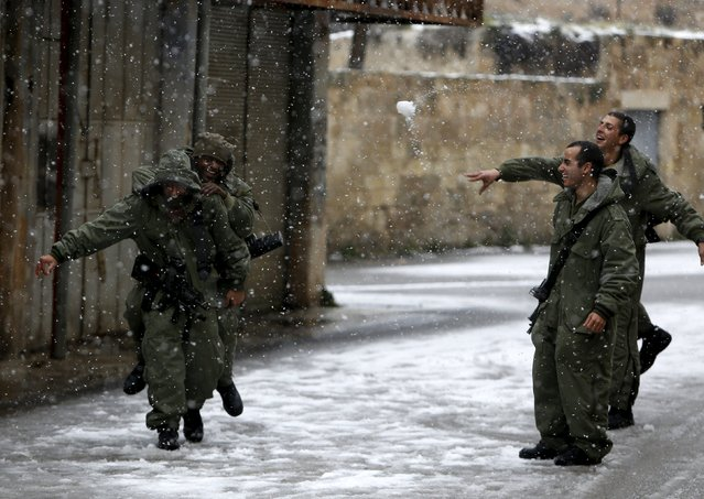 Israeli army soldiers play with snow during a snow storm in West Bank old city of Hebron, January 26, 2016. (Photo by Mussa Qawasma/Reuters)