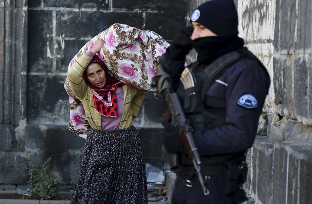A resident carries her belongings past a police officer as she flees from Sur district, which is partially under curfew, in the Kurdish-dominated southeastern city of Diyarbakir, Turkey January 27, 2016. Security forces killed 20 Kurdish militants in southeast Turkey while three Turkish soldiers died in a rebel attack, the military said on Wednesday, as authorities widened a curfew in the mainly Kurdish region's largest city, Diyarbakir. Hundreds of locals, including children and the elderly, fled curfew-bound areas of Diyarbakir's Sur district as gunfire and blasts resounded and police helicopters flew overhead, a Reuters witness said. (Photo by Sertac Kayar/Reuters)