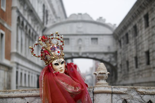 A masked reveller poses in front of the Ponte dei Sospiri (Bridge of Sighs) during the Venice Carnival January 30, 2016. (Photo by Alessandro Bianchi/Reuters)