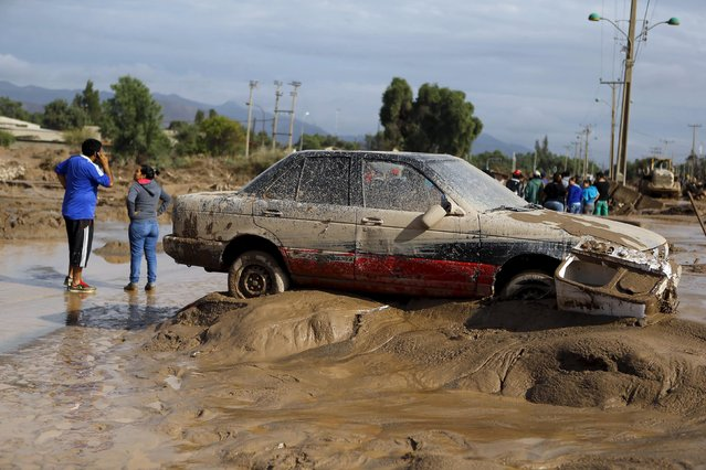 A vehicle covered in mud is pictured on a street at Copiapo city, March 26, 2015. (Photo by Ivan Alvarado/Reuters)