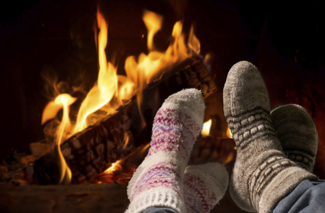 Feet in wool socks warming at the fireplace. (Photo by Alex Raths/Getty Images/iStockphoto)