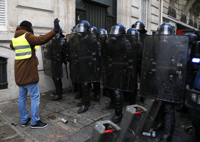 Police officers block a demonstrator wearing yellow vests from entering a street in Paris, Saturday, December 8, 2018. Prized Paris monuments and normally bustling shopping meccas locked down Saturday and tens of thousands of police took position around France, fearing worsening violence in a new round of anti-government protests. (Photo by Thibault Camus/AP Photo)
