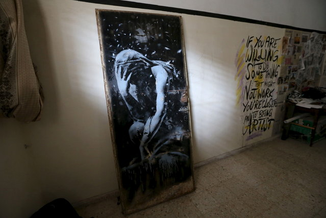 The doorway of a destroyed house, which was painted by British street artist Banksy, is seen inside the gallery of a local Palestinian artist after he bought it from the house's owner, in Khan Younis in the southern Gaza Strip, April 1, 2015. A Palestinian man was lamenting his misfortune on Wednesday after selling his bombed-out doorway to a local artist without realizing that the image painted on it was by Banksy and could be worth a small fortune.  (Photo by Ibraheem Abu Mustafa/Reuters)