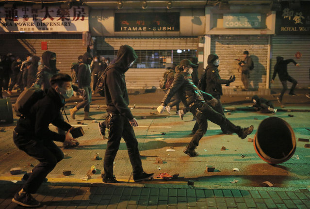 Rioters try to throw bricks and other objects at police in Mong Kok district of Hong Kong, Tuesday, February 9, 2016. (Photo by Vincent Yu/AP Photo)