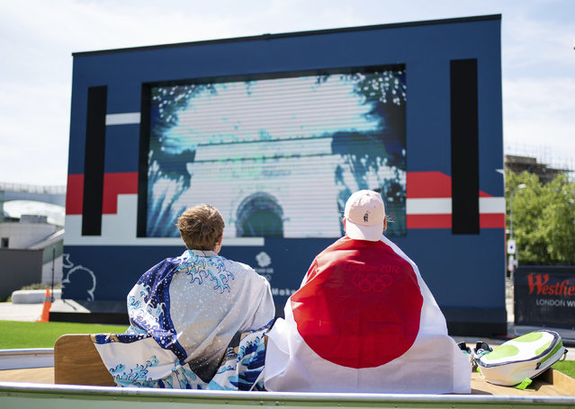Fans watch the opening ceremony of the Tokyo 2020 Olympic Games on a big screen at the Team GB Tokyo 2020 Olympics fanzone, at Westfield, London, Friday July 23, 2021, which will be open for the next 17 days. (Photo by Dominic Lipinski/PA Wire via AP Photo)