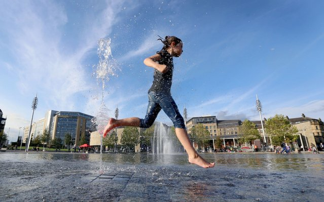 Mischa Fanning of Bradford, West Yorkshire, cools down in City Park, as many parts of the country enjoyed warm weather on October 14, 2017. (Photo by Lorne Campbell/Guzelian)
