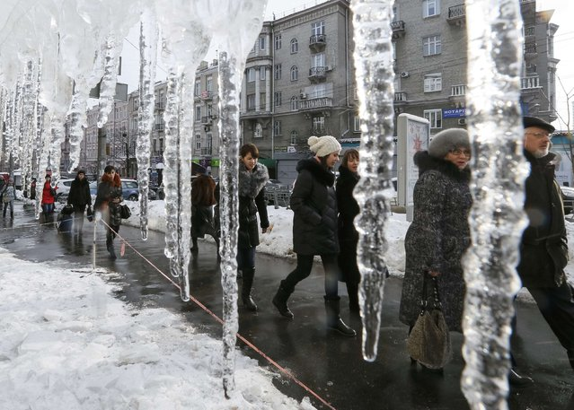 People walk past icicles, which hang from the roof of a building in a street in central Kiev, Ukraine, January 13, 2017. (Photo by Gleb Garanich/Reuters)