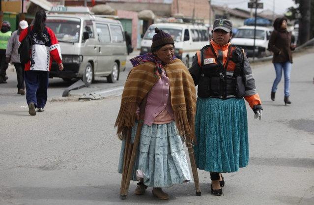 In this December 13, 2013 photo, an Aymara traffic policewomen, right, aids a woman in crossing a street in El Alto, Bolivia. (Photo by Juan Karita/AP Photo)