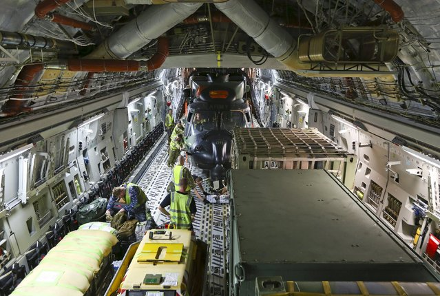 Royal Australian Air Force and Army personnel load a Multi Role Helicopter (MRH 90) onto an RAAF C-17 aircraft before departing from RAAF Base Townsville in Australia, en route to assist in Cyclone Winston-ravaged Fiji, in this handout image supplied by the Australian Defence Force on February 23, 2016. (Photo by Reuters/Australian Defence Force)