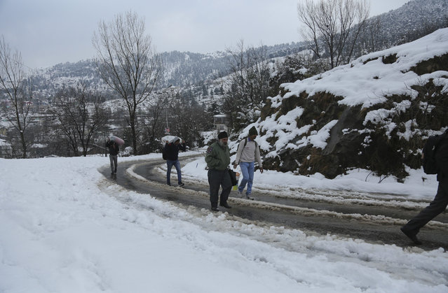 Stranded passengers walk through a snow covered area on the Jammu-Srinagar highway in Kud, about 90 kilometers (56 miles) east of Jammu, India, Monday, January16, 2017. (Photo by Channi Anand/AP Photo)