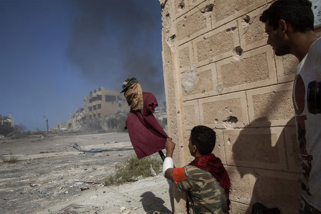 A fighter, supporter of the Libyan Government of National Accord, uses a dummy to catch the attention of Islamic State group snipers at the frontline in Sirte on September 22, 2016. Ten jihadists and nine pro-government fighters died in clashes around the last positions of the Islamic State group in the Libyan coastal city of Sirte, 450 kilometres (280 miles) east of the Libyan capital Tripoli, medical and military sources said. (Photo by Fabio Bucciarelli/AFP Photo)