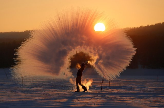 "Winter outdoor sports enthusiast Olesya Ushakova poses while throwing hot water into subzero air as she participates in the ""Dubak Challenge"", an intense cold challenge that is popular on social media in Russia, during sunset outside the Siberian city of Krasnoyarsk, Russia February 8, 2019. (Photo by Ilya Naymushin/Reuters)"