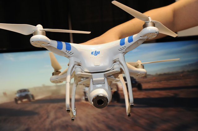 "A DJI Innovations DJI Phantom 2 Vision aerial system drone is shown during ""CES: Unveiled"", the media preview for International CES, at the Mandalay Bay Convention Center January 5, 2014 in Las Vegas, Nevada. The Phantom 2 Vision, available for USD 1,199, has a 14-megapixel camera on board that can shoot raw photos and 1080p video. (Photo by Robyn Beck/AFP Photo)"