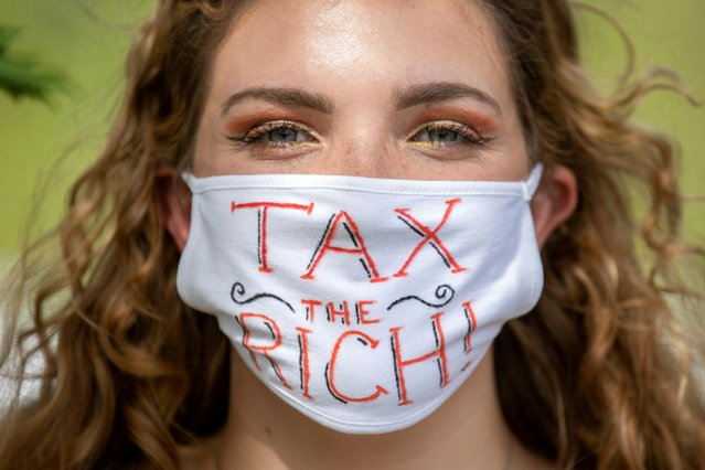 """NDP supporter Sophie Reynolds wears a """"Tax the rich"""" mask during an election campaign visit by New Democratic Party (NDP) leader Jagmeet Singh in Welland, Ontario, Canada on September 15, 2021. (Photo by Nick Iwanyshyn/Reuters)"""