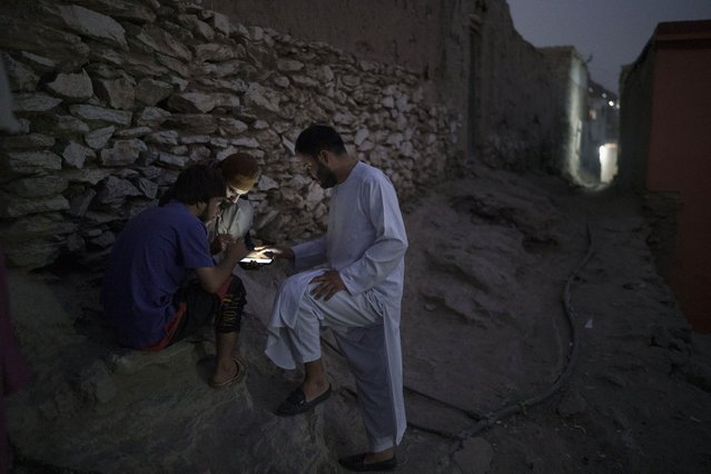Afghans play games on a cellphone outside their home in Kabul, Afghanistan, Saturday, September 11, 2021. (Photo by Felipe Dana/AP Photo)