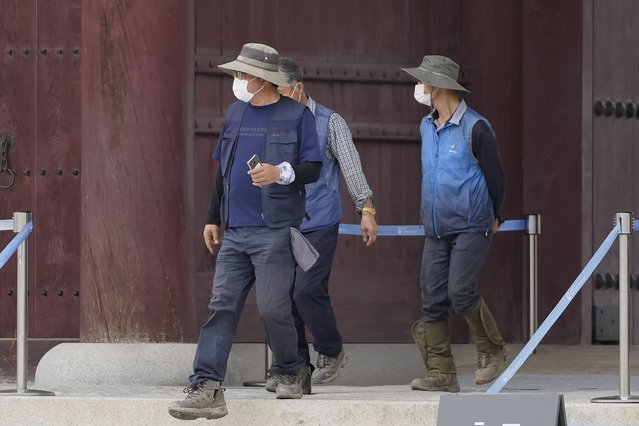 Workers wearing face masks to help curb the spread of the coronavirus walk down steps at the Gyeongbok Palace, one of South Korea's well-known landmarks, in Seoul, South Korea, Friday, September 17, 2021. (Photo by Lee Jin-man/AP Photo)