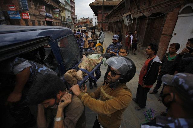 Volunteers carry an injured woman after an earthquake in Kathmandu, Nepal, Saturday, April 25, 2015. (Photo by Niranjan Shrestha/AP Photo)