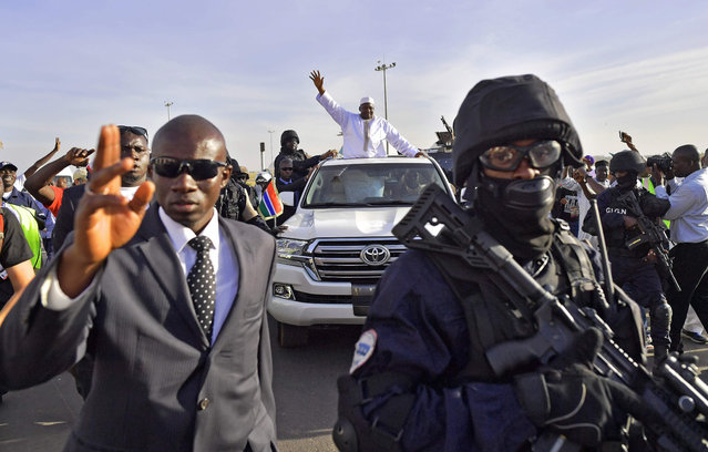 Gambia' s new president Adama Barrow (C) waves as he leaves Banjul airport on January 26, 2017 in Banjul, after returning from Senegal Jubilant Gambians on Janauary 26 welcomed home their new President Adama Barrow, who was elected almost two months ago but forced to flee to Senegal when his predecessor refused to step aside. Dressed in flowing white robes and cap, Barrow stepped off the plane, with heavily- armed troops from Senegal and Nigeria standing by as he flew in from Dakar where he had taken shelter on January 15. (Photo by Carl de Souza/AFP Photo)