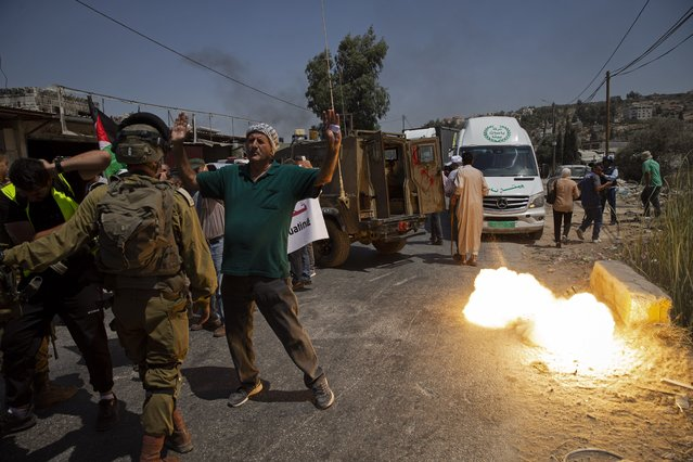 A sound grenade is fired by Israeli forces during a protest against the creation of a new road for Israeli settlers, near the Palestinian village of Beita, north of the West Bank city of Nablus, Wednesday, August 25, 2021. (Photo by Majdi Mohammed/AP Photo)