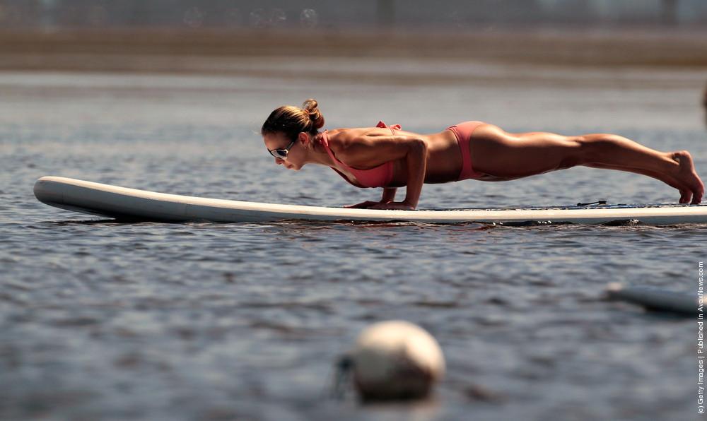 Practioners Enjoy Serenity Of Paddleboard Yoga