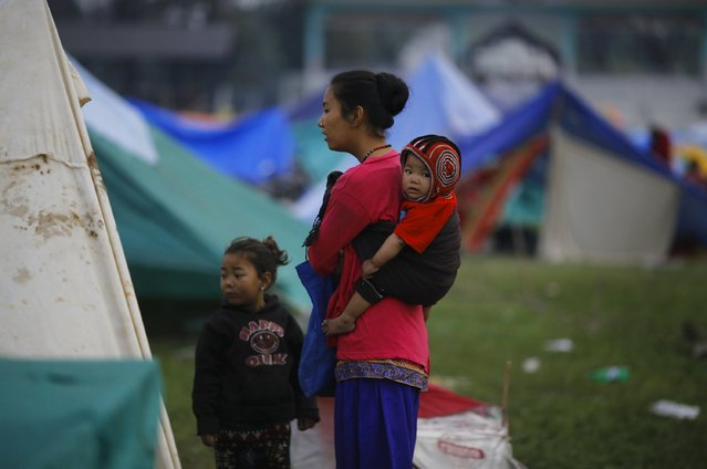 An earthquake victim carries her baby on her back as she stands outside her makeshift shelter on open ground in the early hours in Kathmandu, Nepal April 28, 2015. (Photo by Adnan Abidi/Reuters)