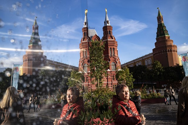 People reflected in a mirror as they walk in Manezhnaya Square decorated for the Day of Moscow celebrating with the Kremlin Wall and the Historical Museum in the background in Moscow, Russia, Sunday, September 5, 2021. (Photo by Alexander Zemlianichenko/AP Photo)