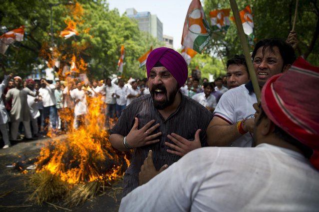 Indian farmers and Youth Congress party activists burn destroyed wheat as they protest against the government in New Delhi, India, Monday, April 27, 2015. The protestors alleged the government was not supporting farmers who lost their crop to unseasonal rains and hailstorms in several Indian states. (Photo by Saurabh Das/AP Photo)
