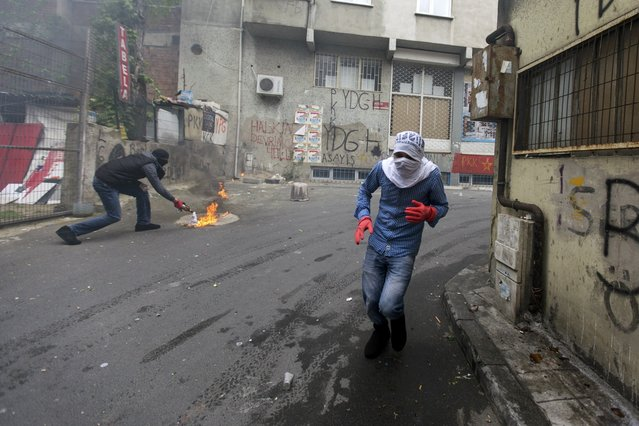 A protester runs during clashes with police in Okmeydani neighborhood in Istanbul, Turkey, May 1, 2015. (Photo by Kemal Aslan/Reuters)