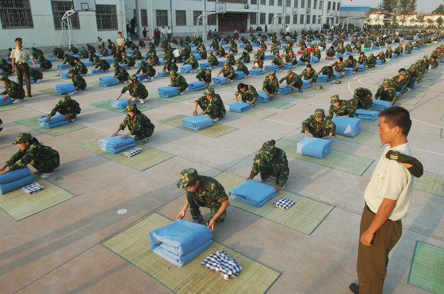 Students take part in a quilt-folding competition after a week-long military training at a middle school in Tancheng, east China's Shandong province September 6, 2007. (Photo by Reuters/China Daily)