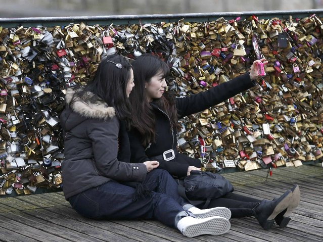 "Tourists make a ""selfie"" picture in front of padlocks clipped by lovers on the Pont des Arts over the River Seine in Paris. (Photo by Charles Platiau/Reuters)"