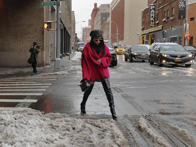 A woman sidesteps slush as she crosses a street on her way to a fashion show at the Skylight Clarkson Square during fashion week, Thursday, February 9, 2017, in New York. (Photo by Julie Jacobson/AP Photo)