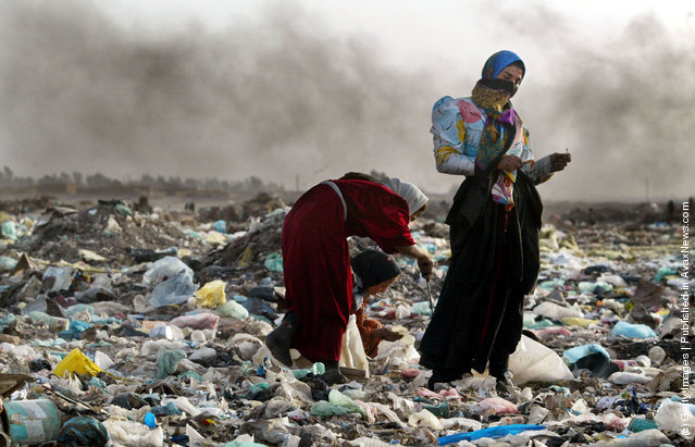 A woman pauses as a girl searches through trash in the garbage dump where their family lives in Baghdad, Iraq