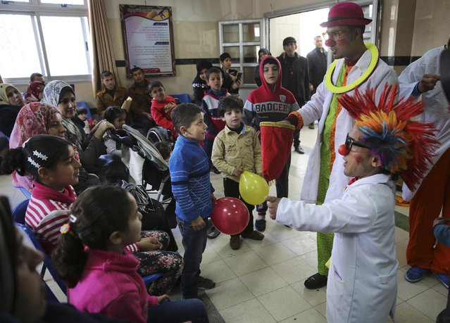 In this Thursday, March 17, 2016 photo, Palestinian clown doctors 24-year-old Majed Kaloub, top right, and 33-year-old Alaa Miqdad, right, perform for children during their visit at the waiting room at Al-Rantisi children's hospital in Gaza City. Majed and Alaa were not trained in hospital clowning, but they grew up in a place that saw three large-scale military conflicts between Israel and Gaza's Hamas rulers in the past decade, let alone dozens of smaller rounds of violence. Both visit three medical centers in the Gaza Strip a week and spend two days at Al-Rantisi, a specialized hospital for children with chronic illnesses. (Photo by Adel Hana/AP Photo)