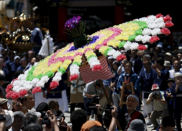 A local resident carries a flower umbrella to lead a portable shrine at the Kanda-Myojin shrine during the Kanda festival in Tokyo, Japan, May 10, 2015. (Photo by Yuya Shino/Reuters)