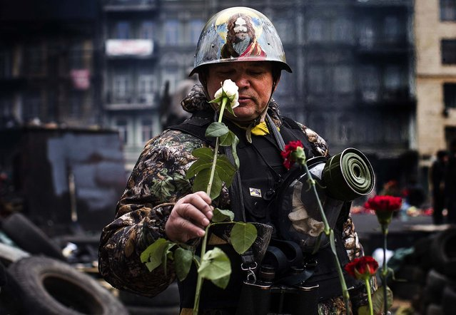 """A militia member stationed at a barricade near Independence Square in Kiev smells the flowers at a memorial to those killed in clashes with police the week before, on February 28, 2014. Former president Viktor Yanukovych gave a press conference Friday from Rostov-on-Don, Russia, calling his ouster a """"gangster coup"""" and saying the secessionist unrest in Crimea was a natural reaction to events in Kiev. (Photo by Uriel Sinai/The New York Times)"""