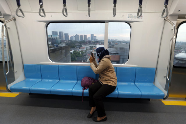 In this March 15, 2019, photo, a passenger takes a photo from inside Mass Rapid Transit (MRT) during a trial run in Jakarta, Indonesia. (Photo by Tatan Syuflana/AP Photo)